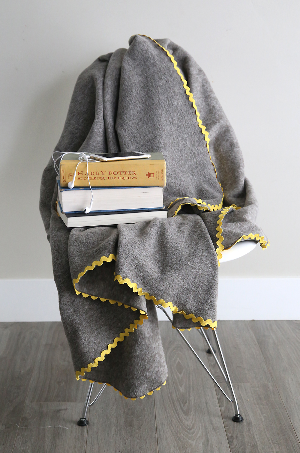 DIY Fleece blanket draped over a chair with books
