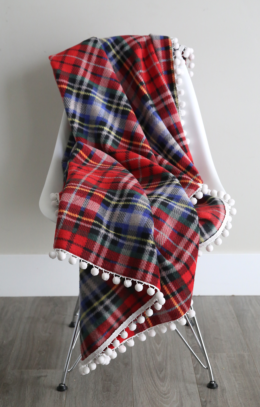 DIY fleece blanket trimmed with pom poms draped over a chair