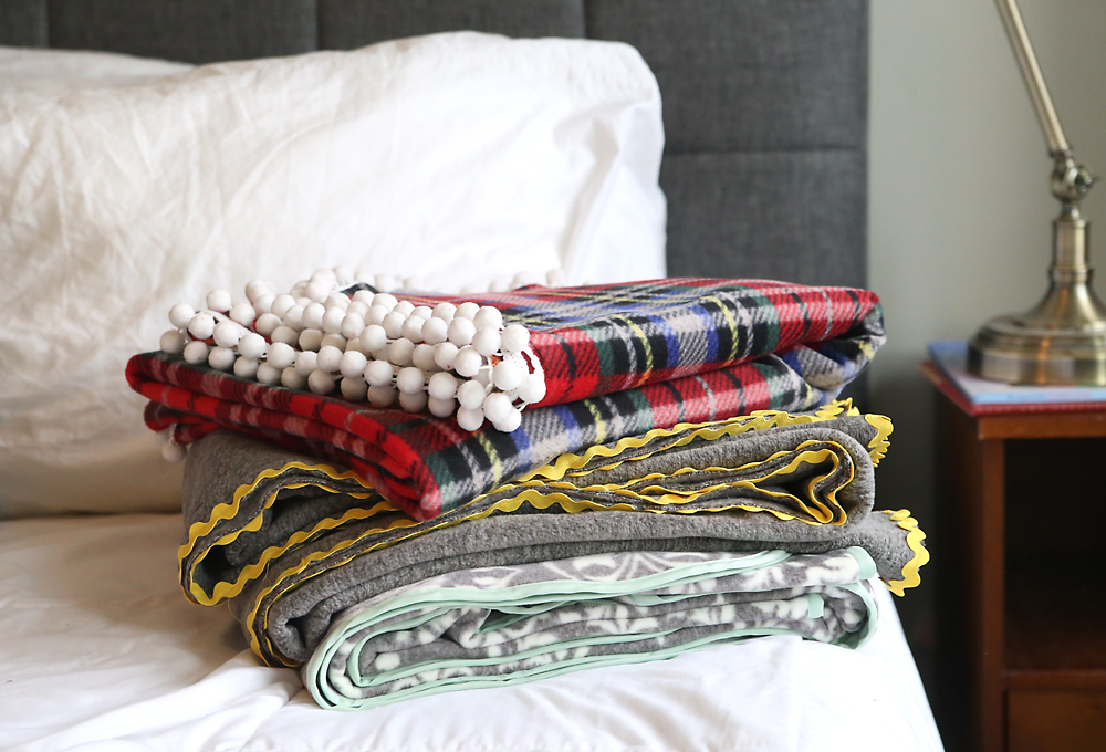 Three DIY fleece blankets folded on a bed