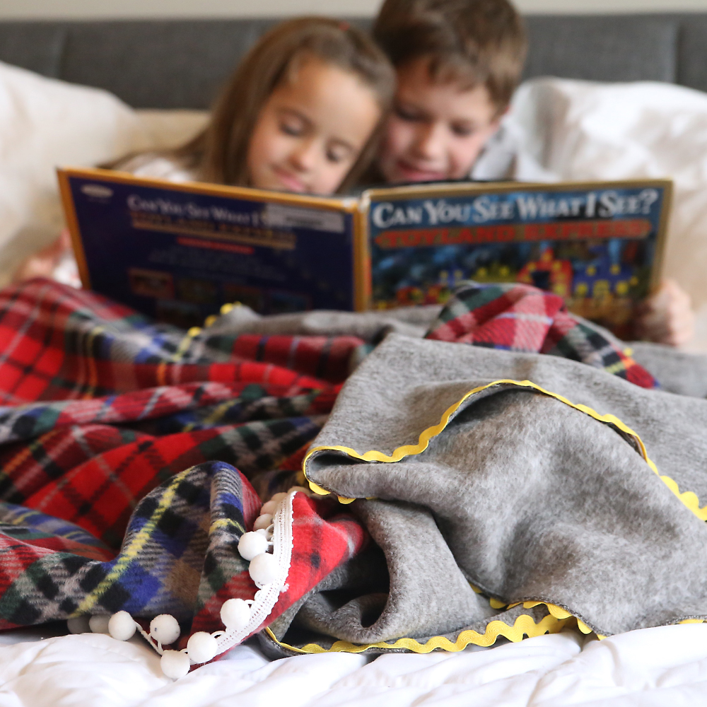 Little kids reading a book with homemade fleece blankets