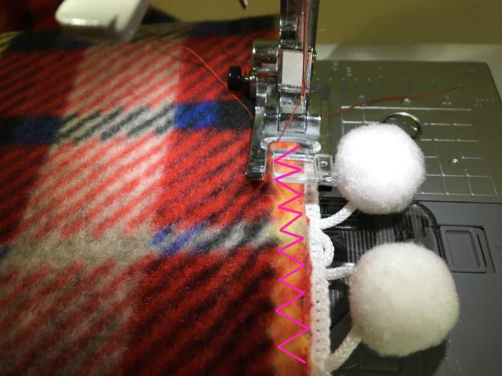 Fleece and pom pom trim on the sewing machine, making a zig zag stitch