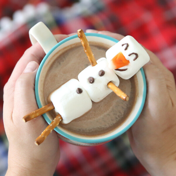 hands holding mug of hot cocoa with marshmallow snowman floating in it