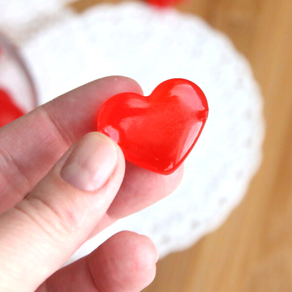 Hand holding a red cinnamon heart hard candy