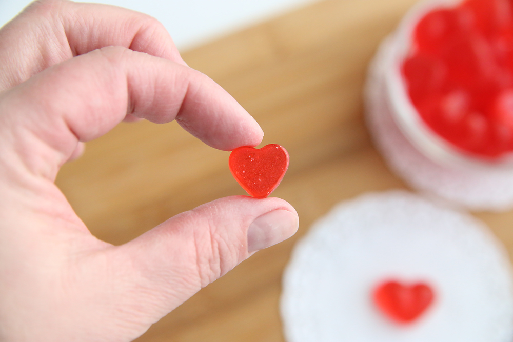 Hand holding a tiny cinnamon heart hard candy