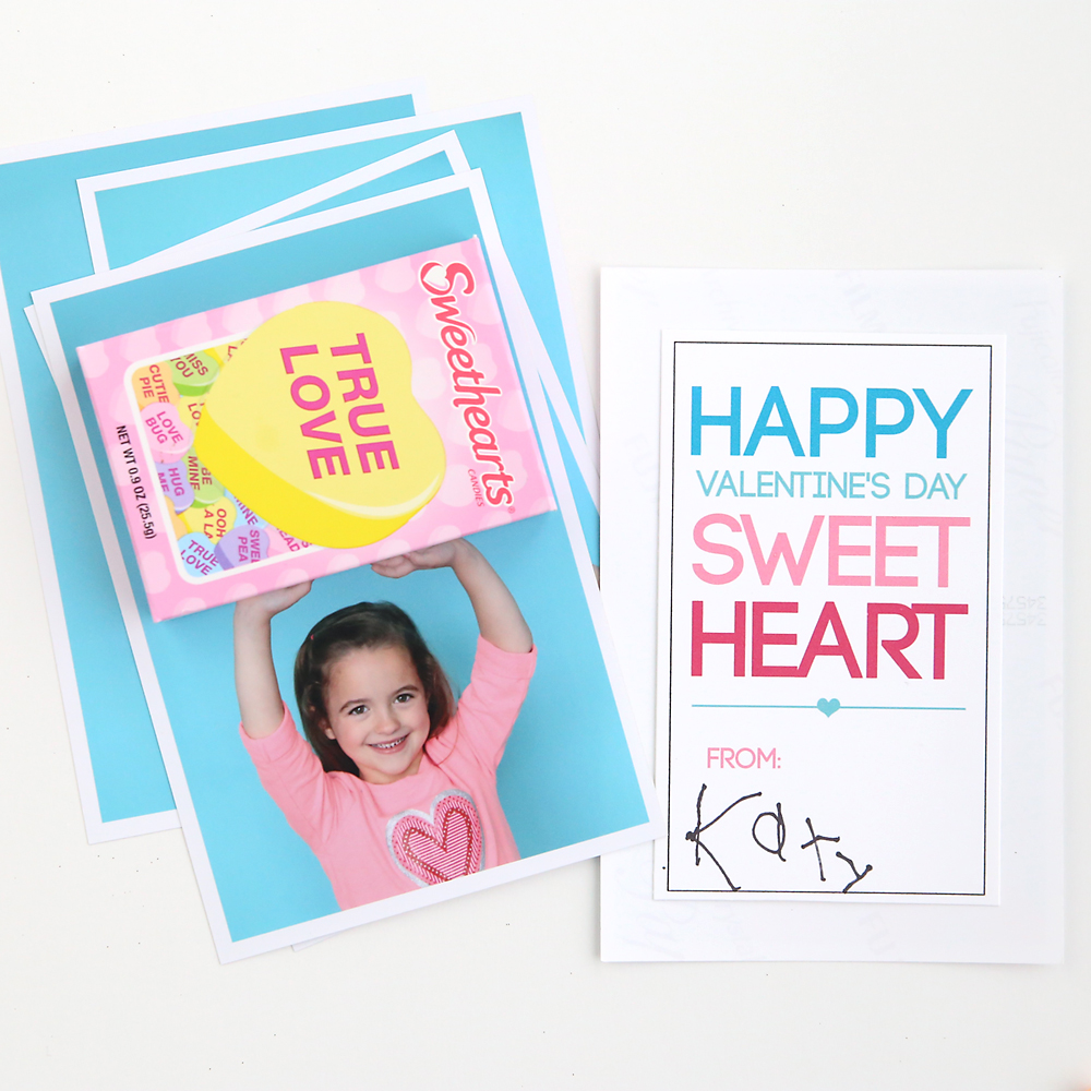 Photo of a little girl with her arms above her head with a box of Sweethearts candy attached so it looks like she\'s holding the box; sweetheart Valentine\'s card