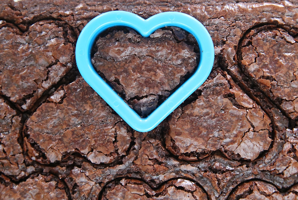 Herat cookie cutter cutting hearts out of sheet of brownies