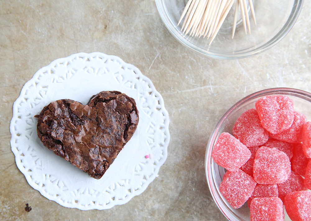 a heart brownie on a doily, with toothpicks and jelly heart candies