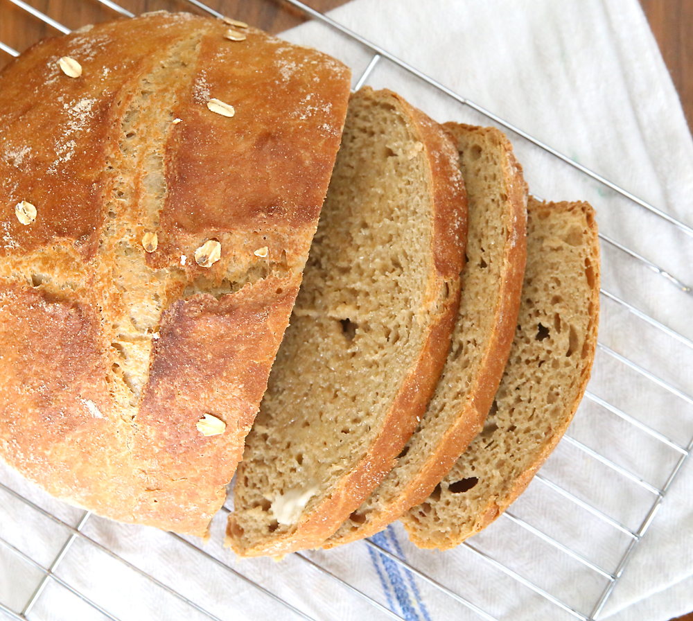 Loaf of whole wheat artisan bread sliced on a cooling rack