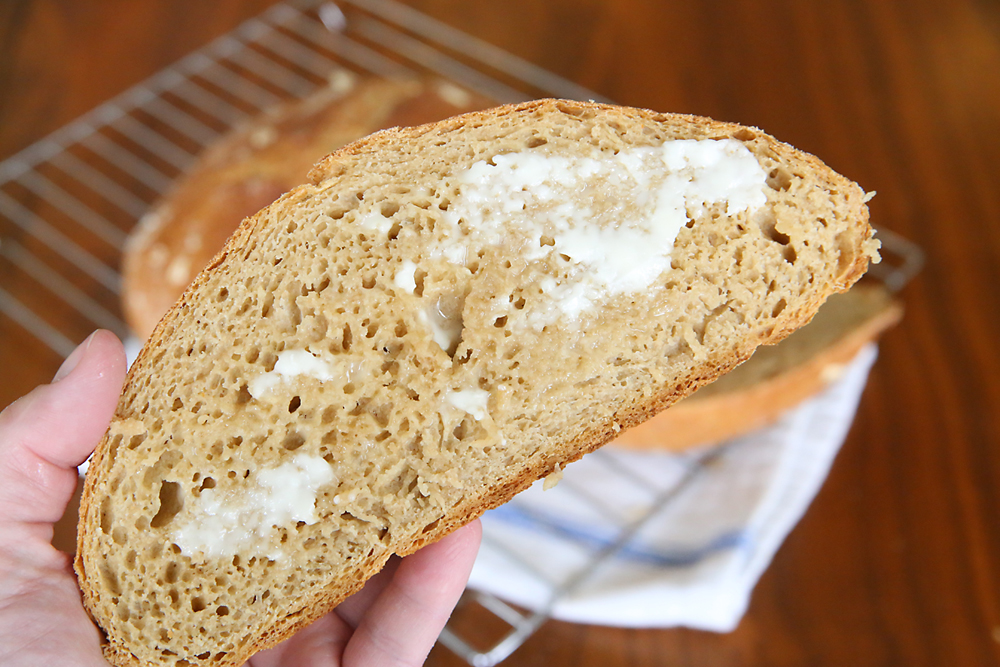 A piece of whole wheat bread spread with butter
