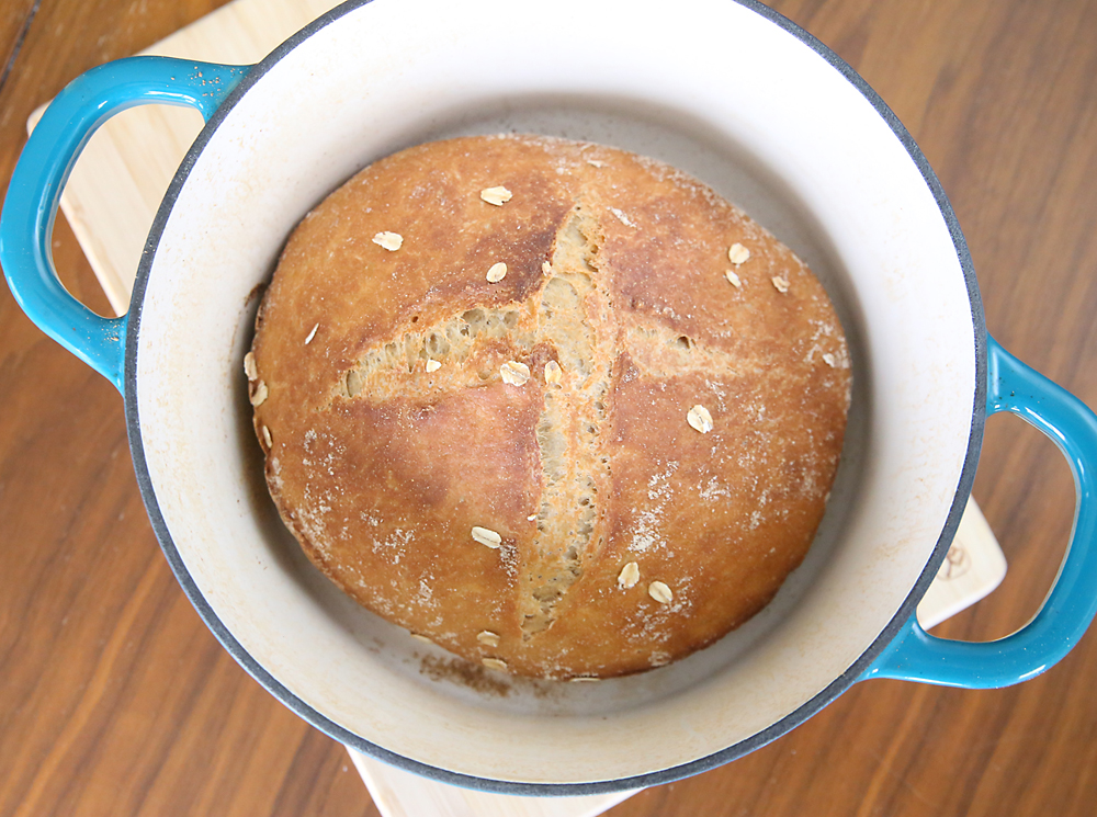 A loaf of whole wheat artisan bread in a dutch oven