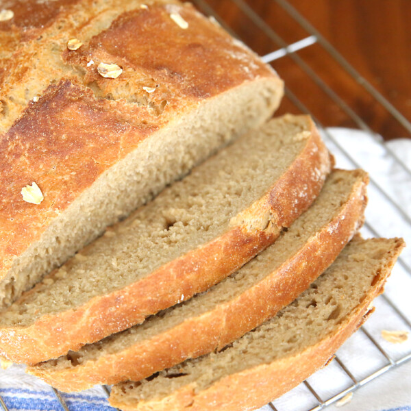 Whole wheat artisan bread sliced on a cooling rack