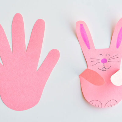 handprint shape cut from pink paper, then folded and decorated to look like a bunny