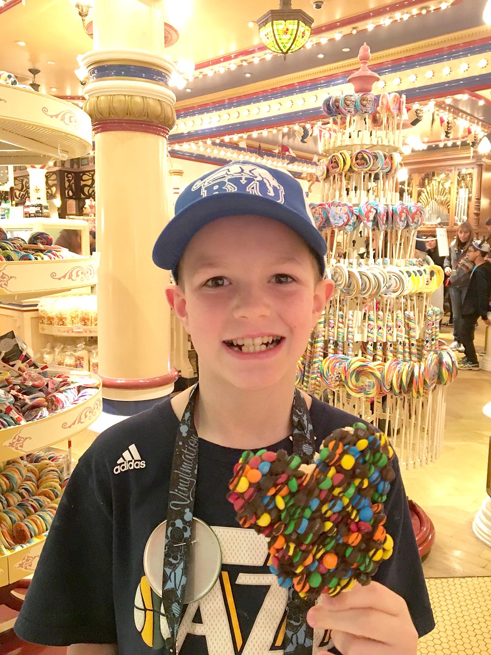 A boy holding a Mickey Mouse rice krispie treat at Disneyland