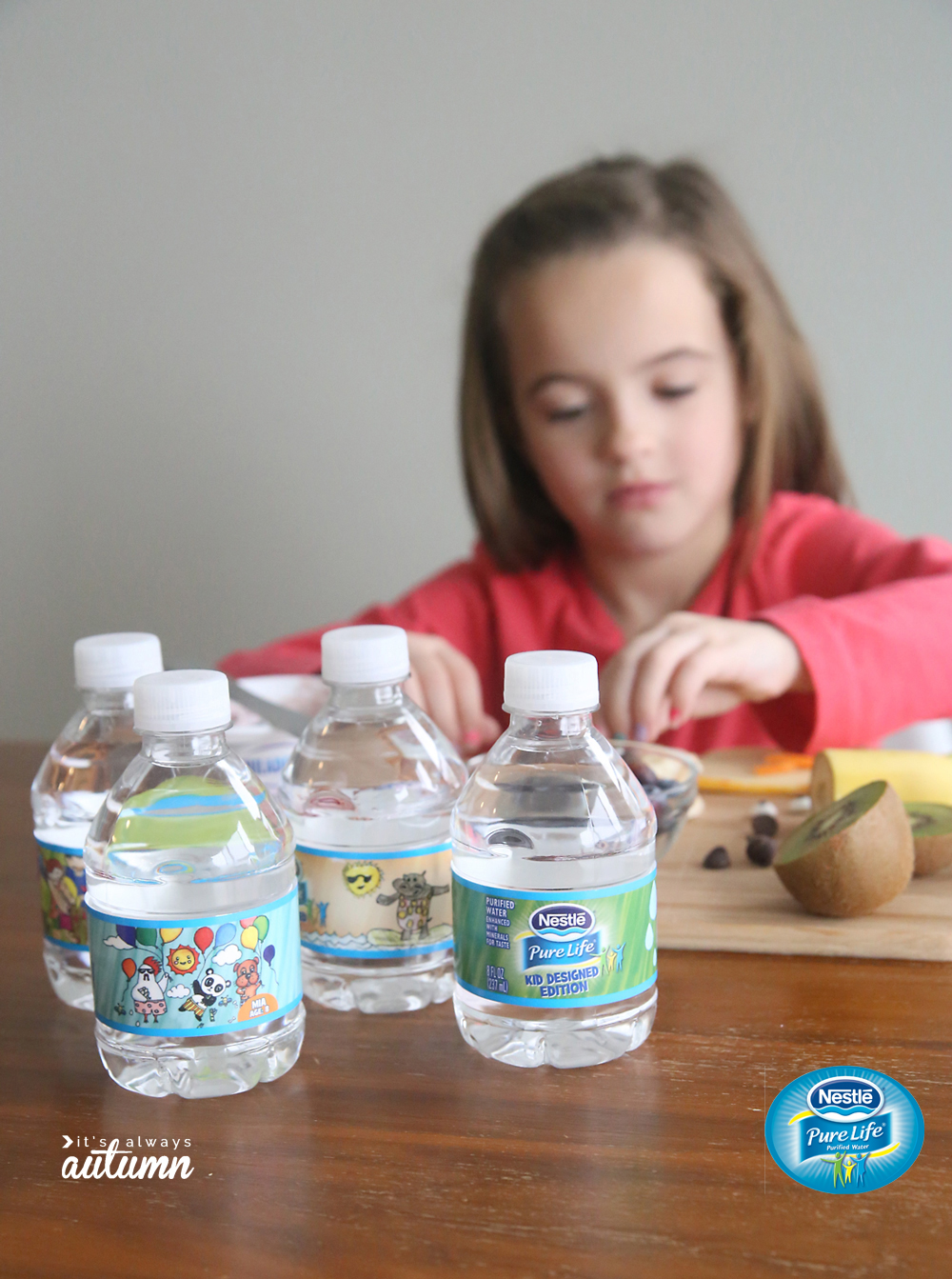 A little girl sitting at a table with water bottles