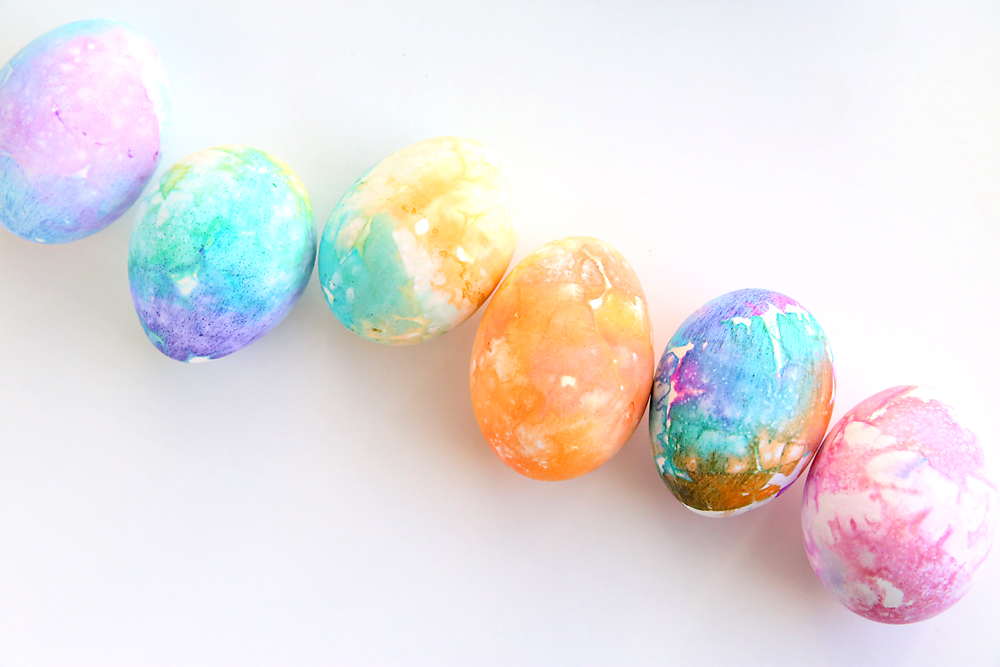 A row of Easter eggs dyed pretty colors using tissue paper
