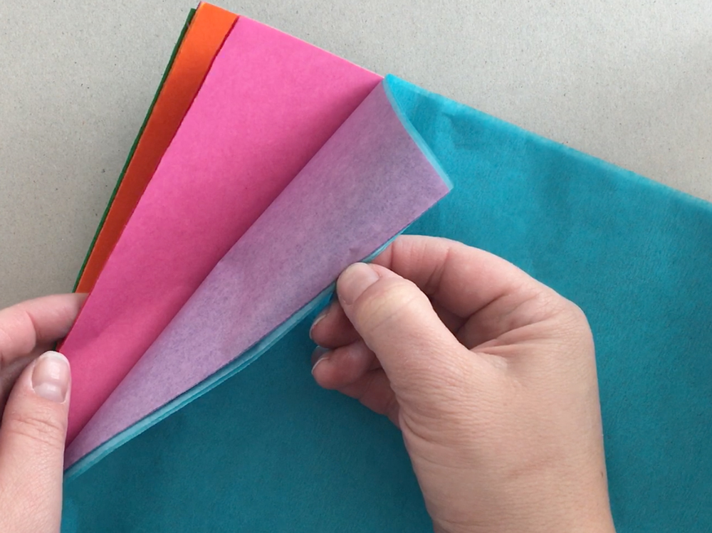 Hands holding various colors of tissue paper