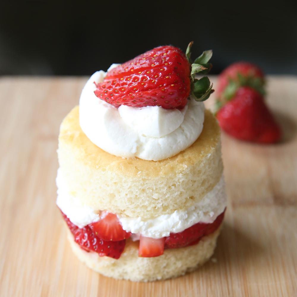 Round piece of strawberry shortcake on a wood cutting board