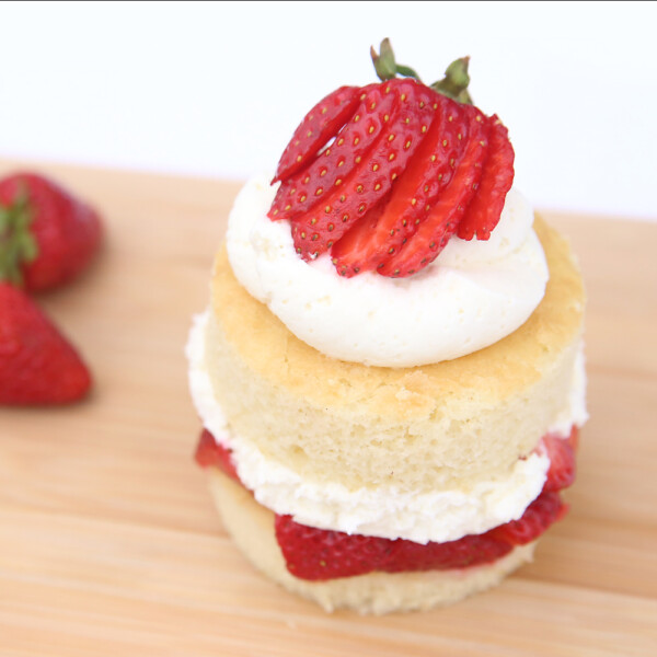 A piece of strawberry shortcake with sliced berry on top