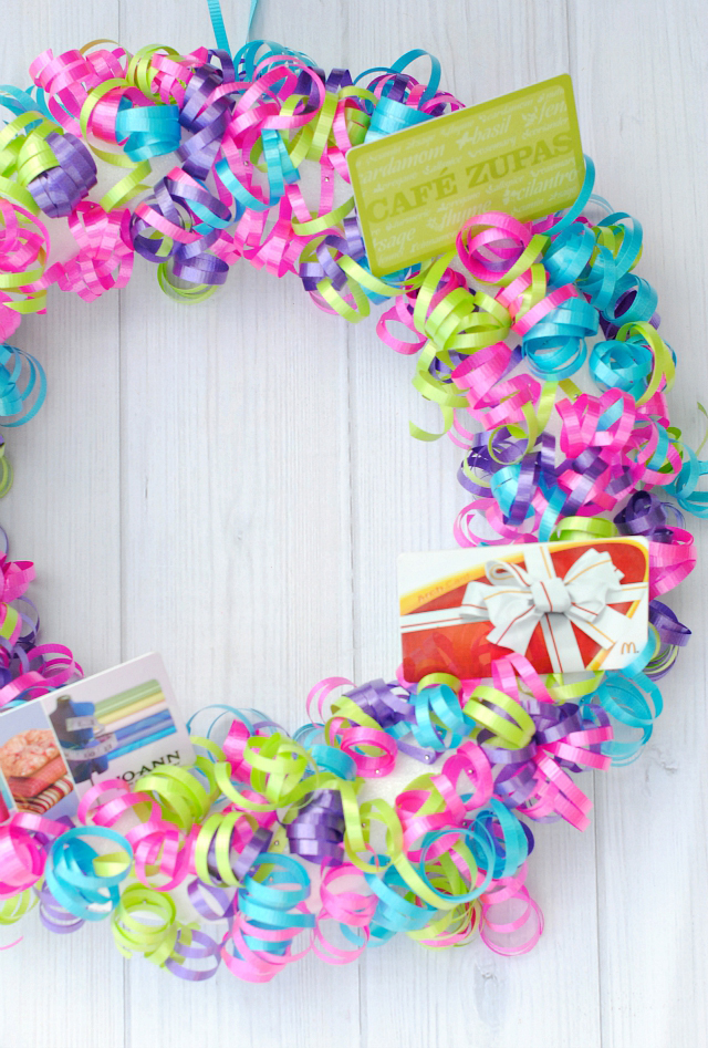 A wreath covered in colorful ribbon with multiple gift cards attached for teacher