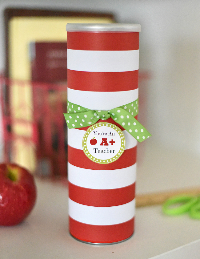 Pringles can covered in striped red and white paper with a tag for a teacher