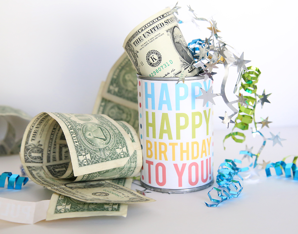 Happy happy birthday sign on a poptop can that\'s been opened to show a roll of one dollar bills