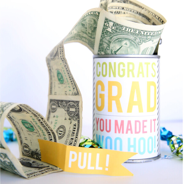 Tin can decorated with congrats grad wrapper, with roll of dollar bills coming out of it