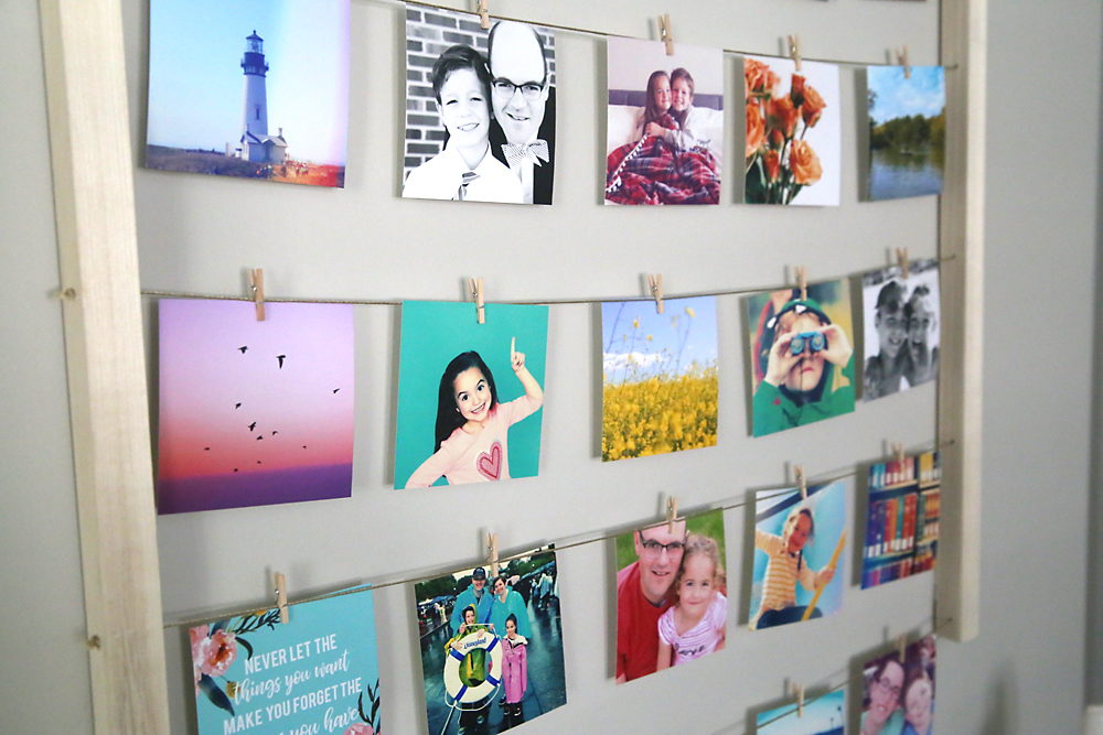 Photos hanging on lines of twine with mini clothespins