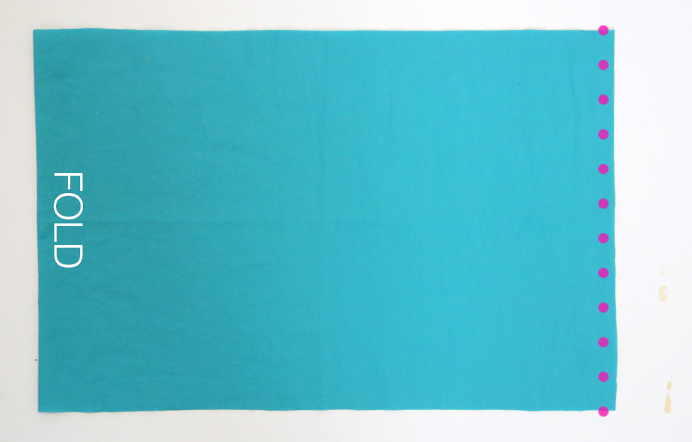 Wide piece of blue fabric folded in half with side seam marked