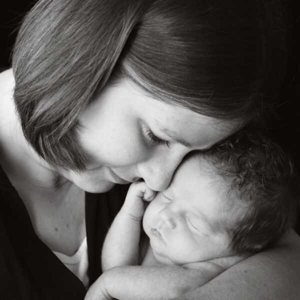 Black and white photo of mother snuggling her baby