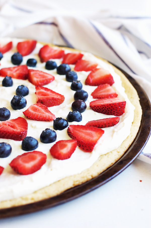 Cookie pizza topped with cream and red and blue berries