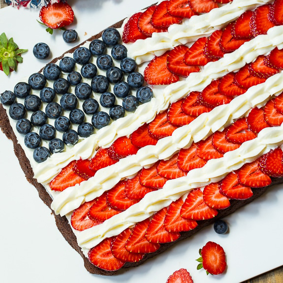 Brownies covered with frosting, strawberries and blueberries to look like an American flag