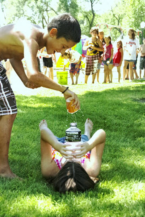 Water games: A boy pouring a cup of water on a girl lying on the grass