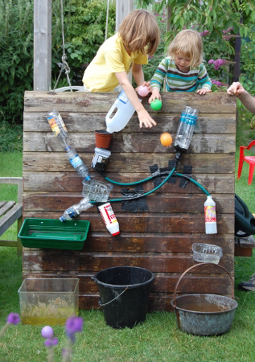 Kids playing with water bottles and tubes attached to a wooden wall