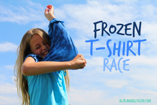 A girl trying to put on a t-shirt that is frozen