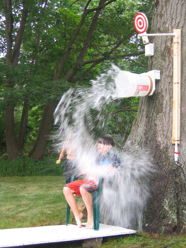 Summer water games: A boy sitting under a bucket of water that is falling on him