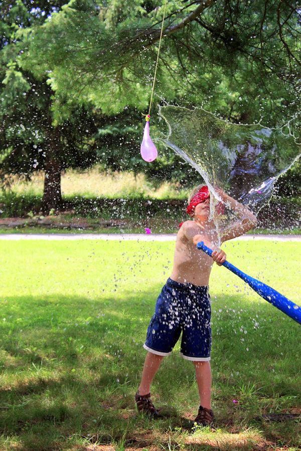 Water games: A young boy using a bat to pop a water balloon