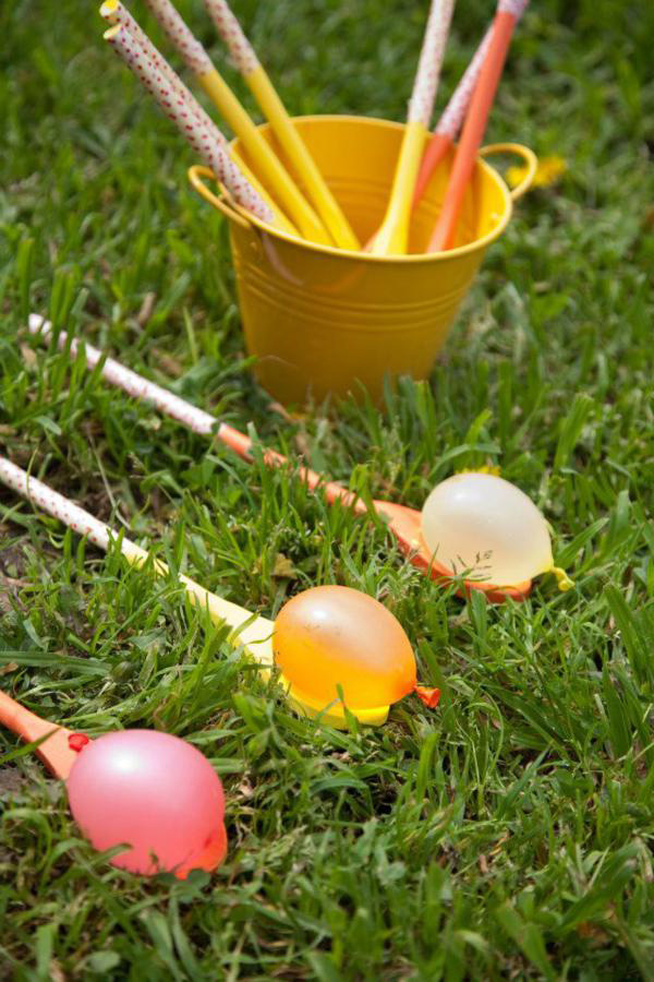 Filled water balloons on wood spoons on the grass
