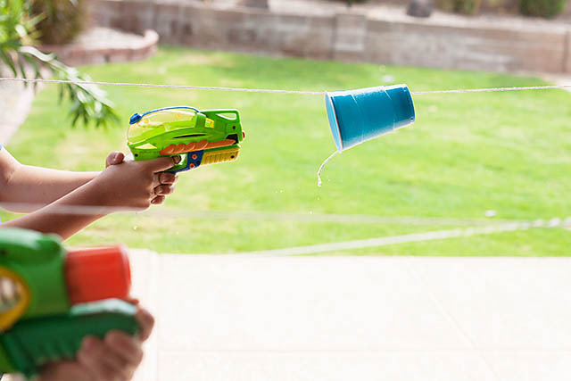 A child shooting a water gun into a cup that\'s suspended on a string