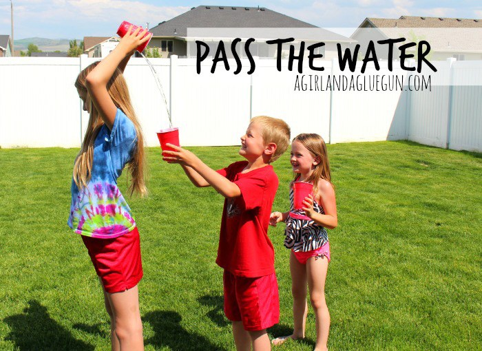Children standing in a row pass water over their heads from cup to cup - summer water games