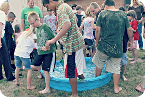 A group of people standing with one foot in a wading pool