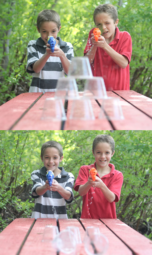 Two boys shooting water guns at a stack of plastic cups