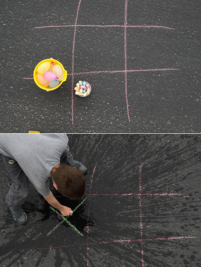 A tic tac toe drawing in chalk on the sidewalk and water balloons