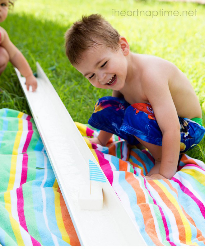 A small child sitting on a beach towel watching small boats in a rain gutter