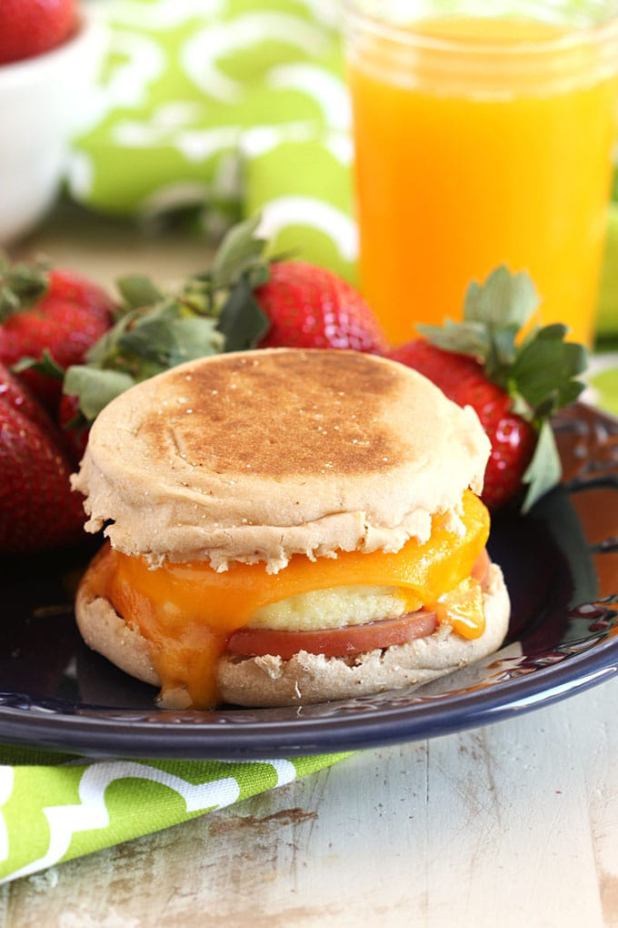 Egg muffin breakfast sandwich on a plate with strawberries