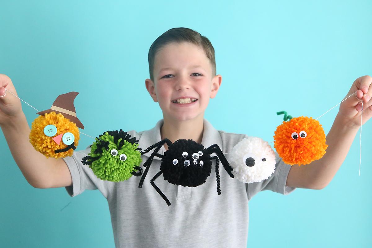 A boy holding a garland of Halloween pom poms