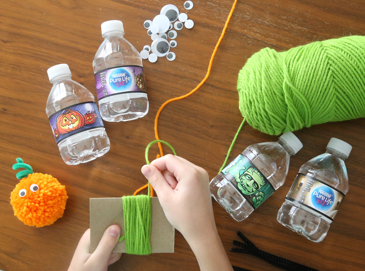 Hands wrapping yarn around small square of cardboard