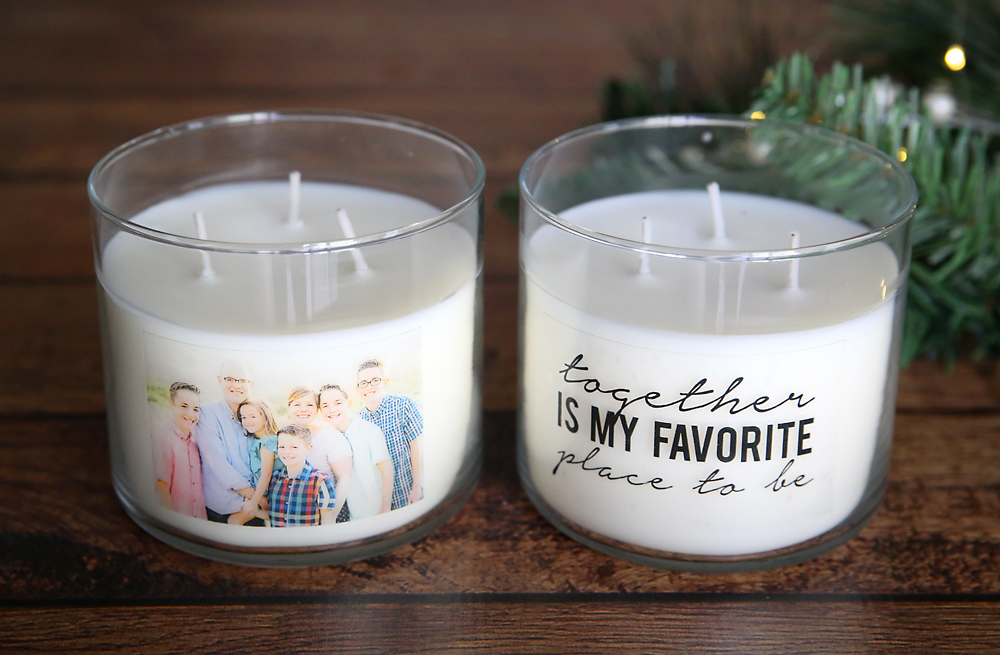 White candle in a glass jar with a photo on the front, second white candle with quote on the front
