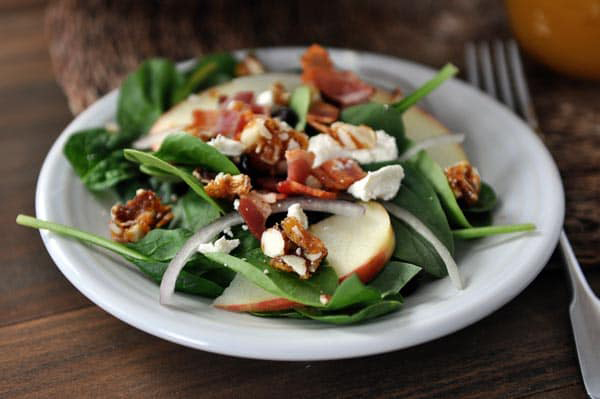 Spinach bacon salad on a plate, with onions and apples