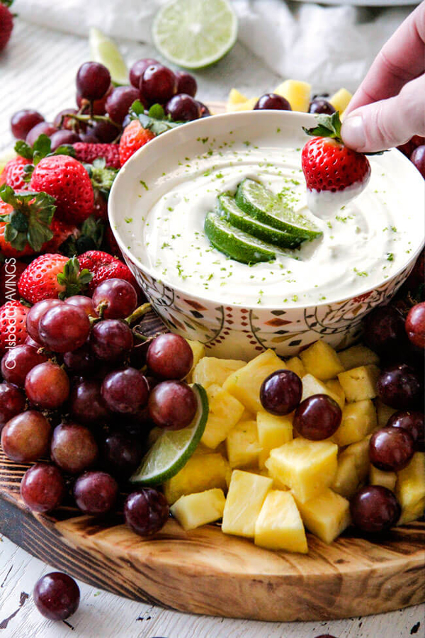 Grapes, pineapple and other fruit on a plate, with a bowl of fruit dip