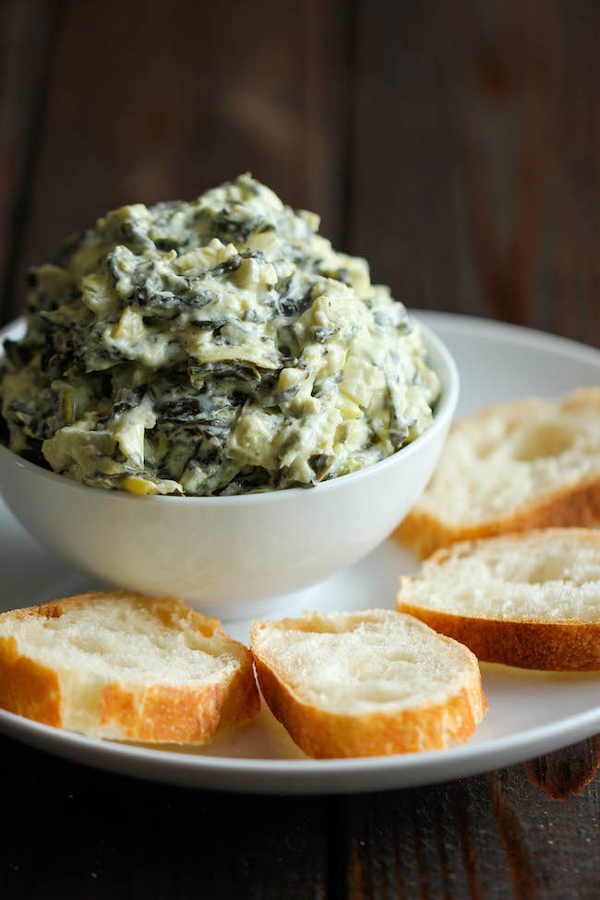 Spinach artichoke dip piled high in a bowl, on a plate with slices of baguette